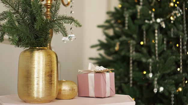 Christmas morning. classic apartments with white interior, decorated tree, candles, christmas decor in gold color