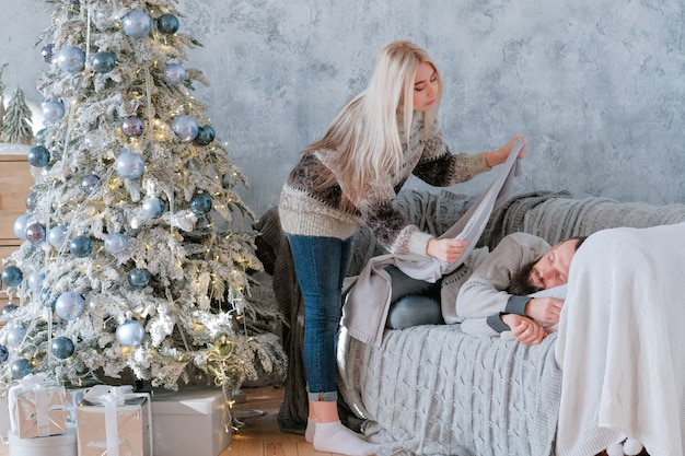 크리스마스 아침. 피곤한 남자 친구에게 담요를 던지는 아가씨는 아늑한 소파에서 잠들었습니다.