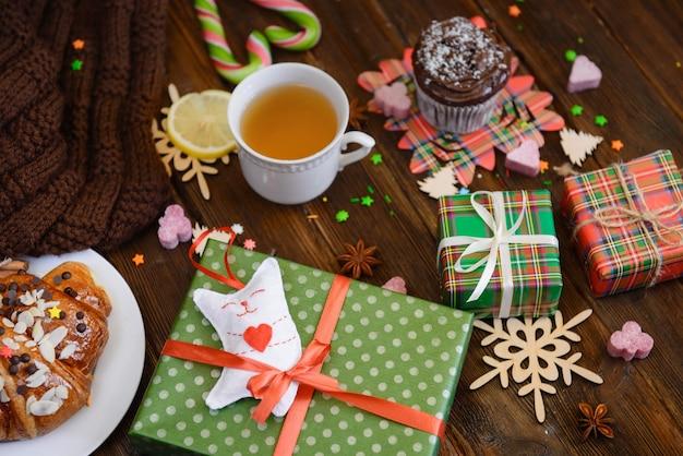 クロワッサン(ベーカリー)、お菓子、ギフトが入ったクリスマスの朝のテーブル。ホリデープレゼント、装飾の上面図。