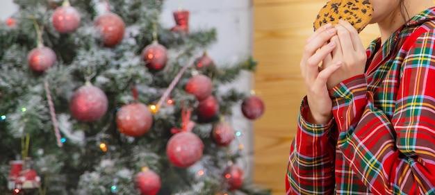 크리스마스 아침, 소녀는 쿠키를 먹습니다. 선택적 초점입니다. 휴일.