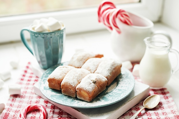 Christmas muffins, milk, cocoa, marshmallows, candy lollipops on a white plate by the window