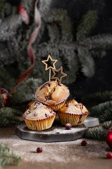 Рождественские кексы с клюквой на деревянном столе темные из еловых веток с новым годом