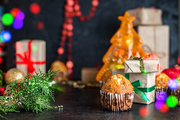 Christmas muffins with decorations on black table