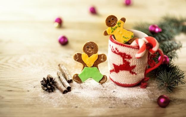 木製の背景に男の形のクリスマスの装飾とクッキーとクリスマスマグカップ