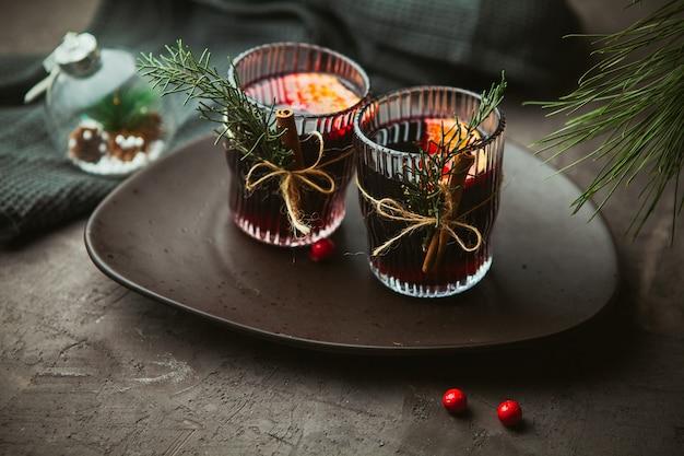 クリスマスは、プレートに香辛料と柑橘系の果物を添えた赤ワインをクローズアップで混ぜ合わせました。クリスマスの時期の伝統的な温かい飲み物