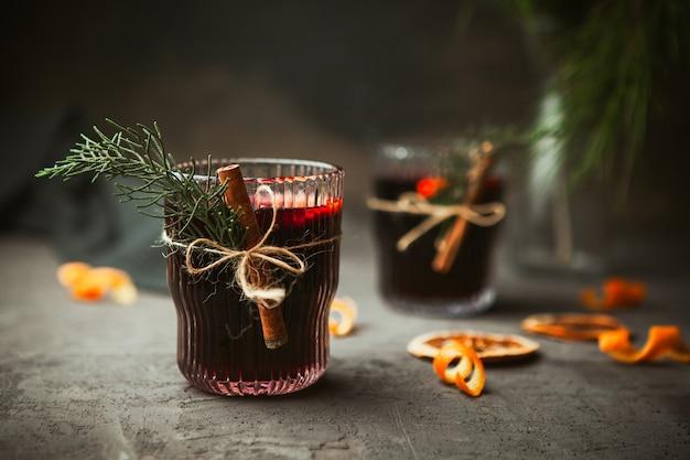 クリスマスは、黒い表面に芳香のあるスパイスと柑橘系の果物を使った赤ワインを混ぜ合わせました。クローズアップ。クリスマスの時期の伝統的な温かい飲み物