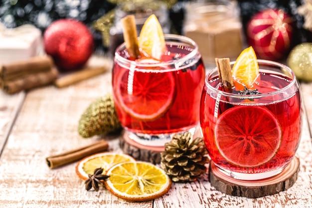 クリスマスは素朴な木製のテーブルの上でスパイスとドライオレンジと赤ワインをグリューワイン。アメリカのクリスマスの伝統的な温かい飲み物