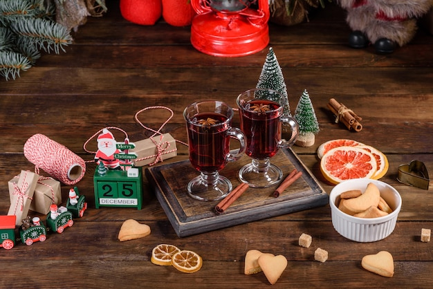 어두운 테이블에 향신료와 과일을 곁들인 크리스마스 mulled 레드 와인. 크리스마스 시간에 전통적인 뜨거운 음료