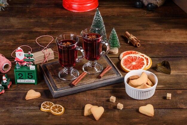 어두운 테이블에 향신료와 과일을 곁들인 크리스마스 mulled 레드 와인.