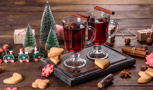 Рождественский глинтвейн красное вино со специями и фруктами на темном столе.