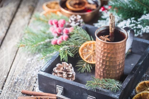 クリスマスは、木製の素朴なテーブルの上でスパイスとフルーツと赤ワインをホットワイン。クリスマスの時期の伝統的な温かい飲み物