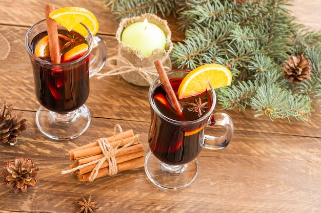 Рождество глинтвейн красное вино со специями и апельсинами на деревянном деревенском столе. традиционный горячий напиток на рождество со свечой
