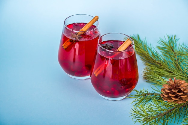 Christmas mulled red wine with spices on blue table. cranberry drink with cinnamon and anise.