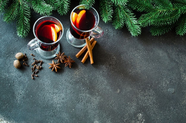 Christmas mulled red wine with spices on dark concrete background