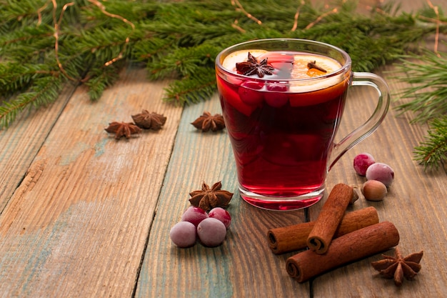 Christmas mulled red wine with spices and oranges on a wooden rustic table.
