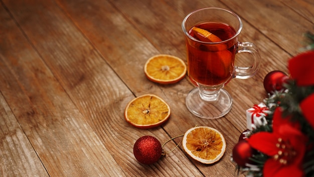 Christmas mulled wine in glass cup on a wooden table with dry oranges