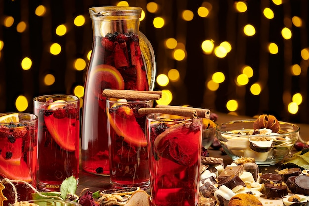 Christmas mulled wine or gluhwein with spices, chocolate sweets and orange slices on rustic table, traditional drink on winter holiday, christmas lights and decorations