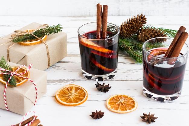 Рождественский глинтвейн. концепция праздника украшена еловыми ветками, подарками и специями.