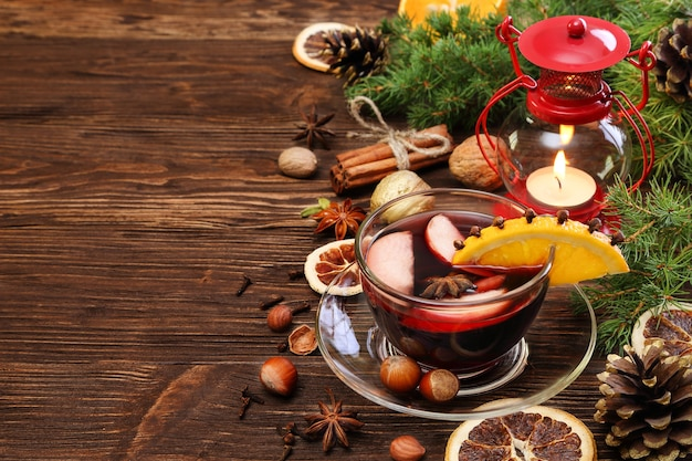 Christmas mulled wine and ingredients on a wooden background, with space for text