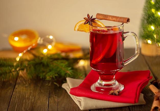 Рождественский глинтвейн красное вино со специями и фруктами на деревянном деревенском столе. традиционный горячий напиток на рождество. горизонтальная рамка