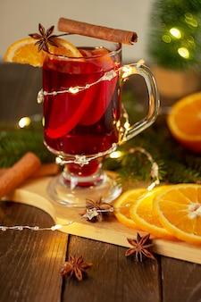Рождественский глинтвейн красное вино со специями и фруктами на деревянном деревенском столе. традиционный горячий напиток для. рождествовертикальная рамка.