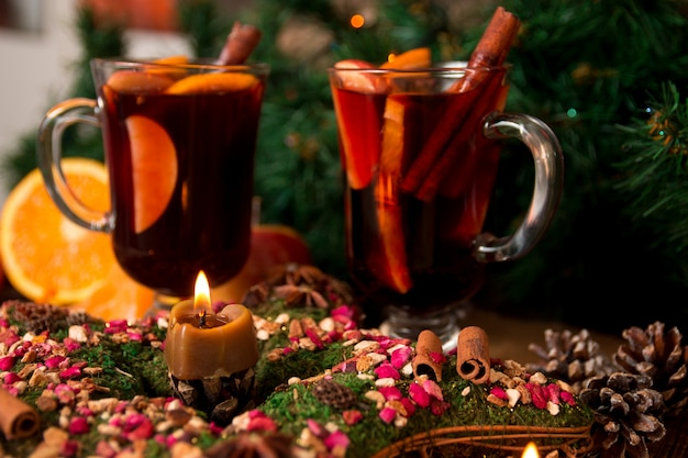 Christmas mulled wine and star anise with candle on wooden table