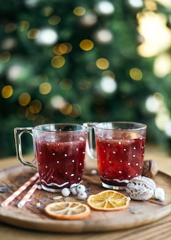 Christmas mulled wine and tea cups, festive composition. decor on a wooden table and a decorated christmas tree. atmosphere of tradition image.