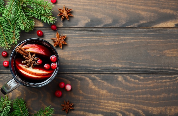 Christmas mulled wine with apple and cranberries. holiday concept decorated with fir branches, cranberries and spices.