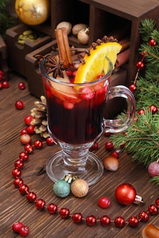 Christmas mulled wine with apple, cranberry, orange, spices and chocolate on a wooden table