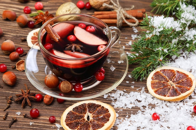 Christmas mulled wine with apple, cranberry, orange and spices on a wooden table