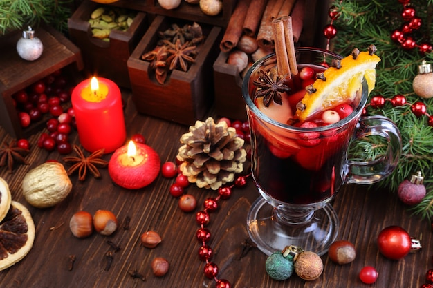 Christmas mulled wine with apple cranberry orange and spices on a wooden table