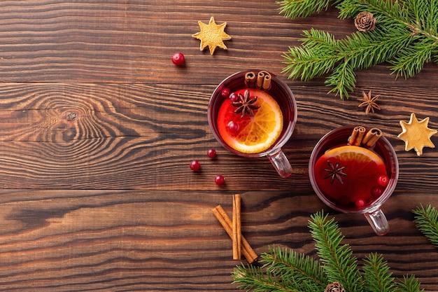 Рождественский глинтвейн с корицей и апельсином в стеклянных кружках возле еловых веток на деревянном столе
