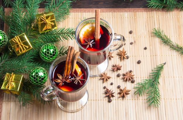 계피와 오렌지를 곁들인 크리스마스 mulled 와인. 테이블에는 가문비나무 나뭇가지와 장난감이 있습니다.