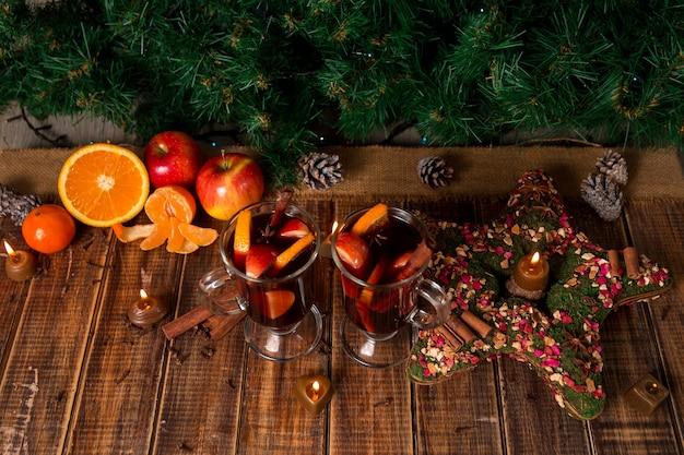 木製のテーブルにフルーツとスパイスとクリスマスグリューワイン
