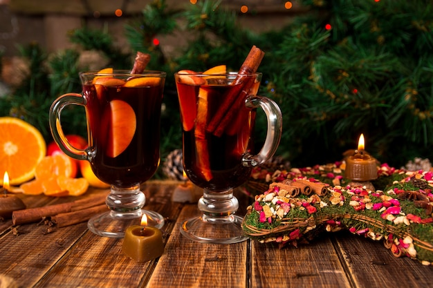 Christmas mulled wine with fruits and spices on wooden table. xmas decorations . two glasses. winter warming drink with recipe ingredients around.