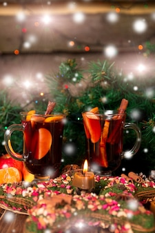 Christmas mulled wine with fruits and spices on wooden table.