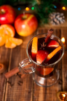 Christmas mulled wine with fruits and spices on wooden table