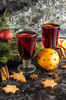 Christmas mulled wine with ginger biscuits orange cinnamon clove anise and fir tree on the dark table