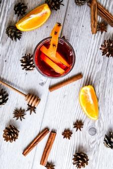 クリスマスは、木製の素朴な背景にスパイスとオレンジのグリューワイン。セレクティブフォーカス。アニスの星とシナモンスティック。クリスマスコーン。テキスト用のスペースをコピーします。上面図