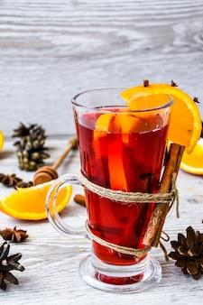 クリスマスは、木製の素朴な背景にスパイスとオレンジのグリューワイン。セレクティブフォーカス。アニスの星とシナモンスティック。クリスマスコーン。テキスト用のスペースをコピーする