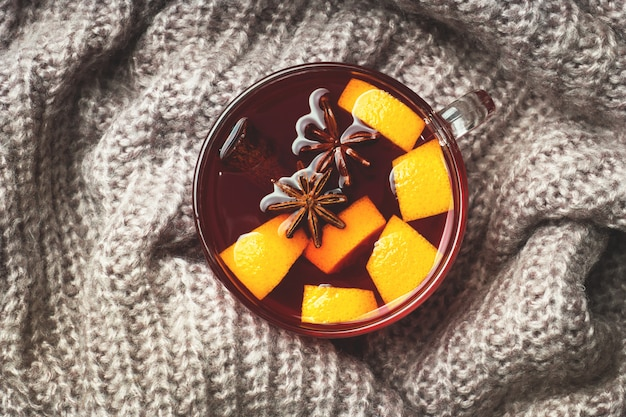 Christmas mulled wine with spices and fruit on a knitted blanket.