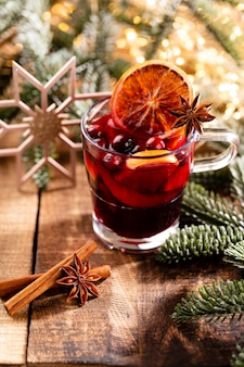 Christmas mulled wine with spices on a wooden rustic table.