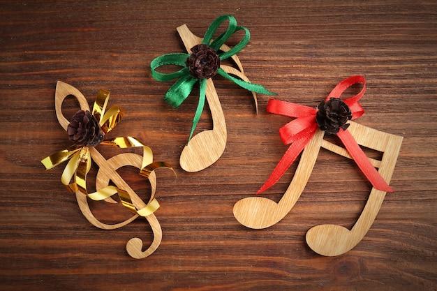 Рождественская музыкальная концепция. декоративный ключ и ноты с бантами на деревянном столе