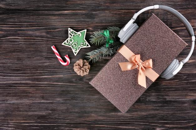 크리스마스 음악 개념입니다. 나무 배경에 헤드폰으로 선물