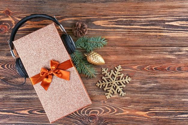 Рождественская музыкальная концепция. подарок с наушниками на деревянной поверхности