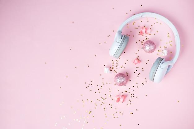 Рождественская музыка или фон подкаста. золотые розовые и белые рождественские украшения и белые наушники на розовом фоне. рождество новый год или вечеринка баннер