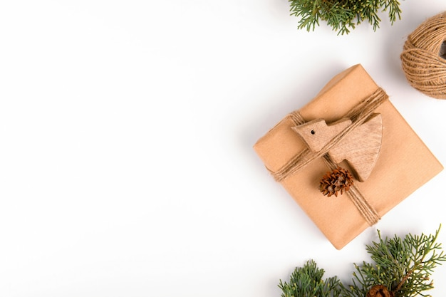 Рождество, натуральные еловые ветки с деревянными игрушками и ремесленный подарок на белом деревянном