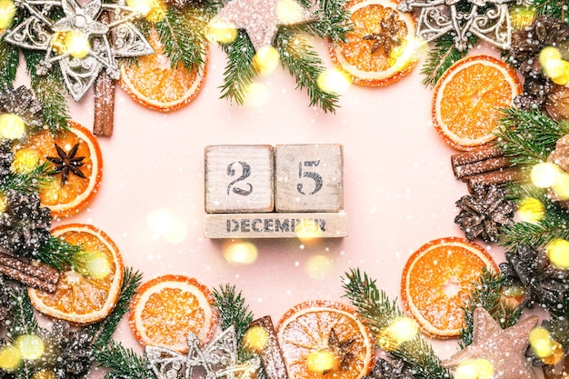 Новогодняя естественная рамка из ломтиков сухих апельсинов и огней боке. календарь 25 декабря