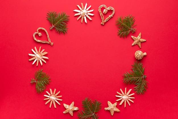 クリスマスの天然木の装飾と赤い背景の松の木のフレーム、コピースペース。フラットレイ、エコロジー素材の装飾品が入ったクリスマスカード、上面図
