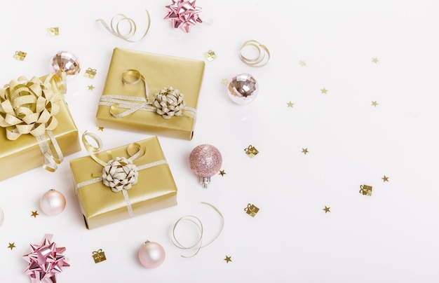 Christmas or ner year holiday composition. festive creative golden pattern, xmas gold decor holiday ball with ribbon, gift, snowflakes, christmas tree on white background. flat lay, top view